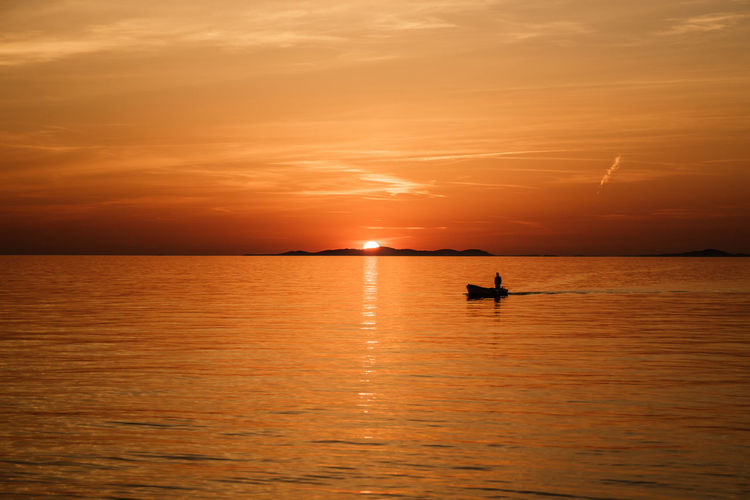 Fisherman coming home on boat during sunset in Croatia Calm Croatia Beauty In Nature Cloud - Sky Fisherman Fishermen Horizon Horizon Over Water Nautical Vessel One Person Orange Color Outdoors Reflection Romantic Sky Scenics - Nature Sea Silhouette Sky Sun Sunset Tranquil Scene Tranquility Transportation Unrecognizable Person Water