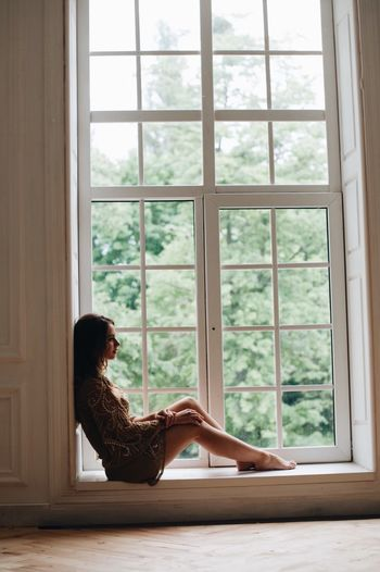 Side view of woman sitting on window sill at home