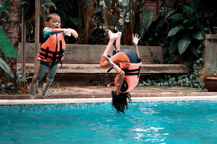 Siblings jumping in swimming pool