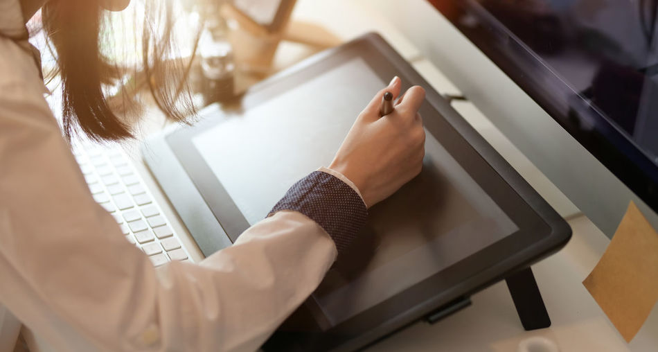 Midsection of woman using graphics tablet and digitized pen on table