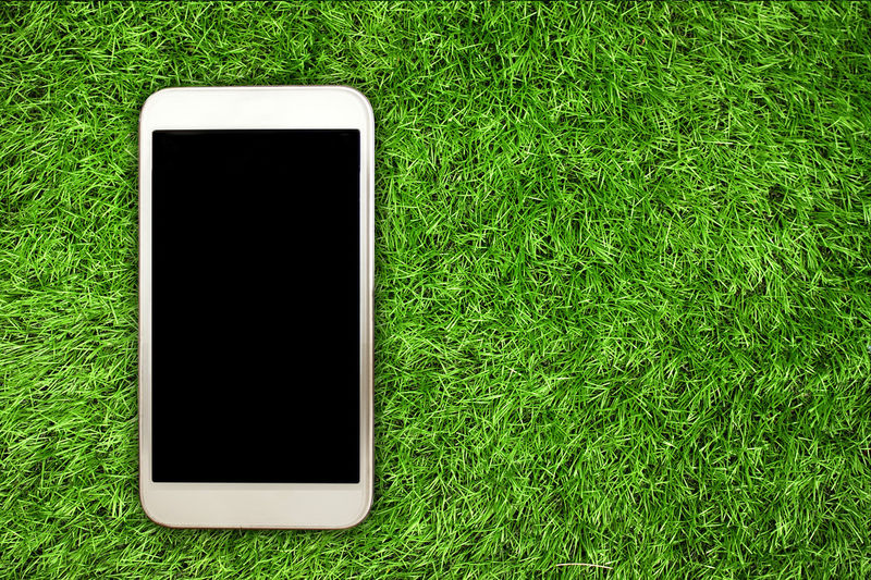 Blank Communication Connection Copy Space Device Screen Field Global Communications Grass Green Color High Angle View Mobile Phone No People Plant Portability Portable Information Device Screen Smart Phone Technology Telecommunications Equipment Touch Screen Wireless Technology