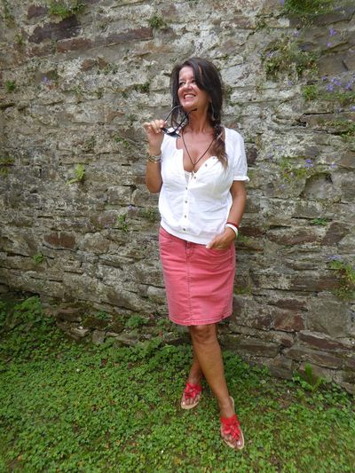 Full length of smiling woman looking away while standing against wall at field