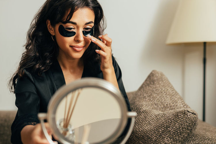 Portrait of young woman holding eyeglasses at home