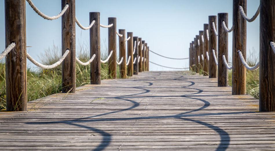 Surface level of wooden boardwalk against sky