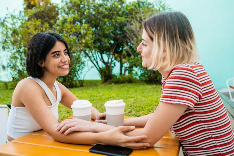Smiling lesbians enjoying coffee on table