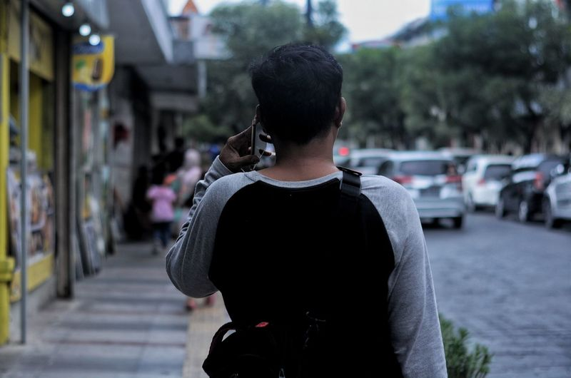 Rear view of man talking on smart phone in city