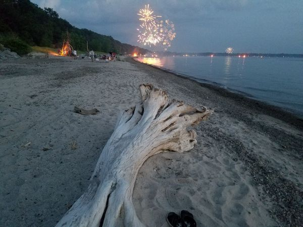 Fireworks In The Sky Log Bonfire Reflections In The Water Night Night On Beach Forth Of July Water Beach Sand Summer Sky Landscape Shore Sandy Beach
