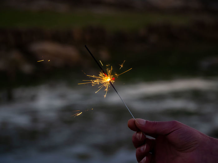 Low angle view of hand holding fireworks