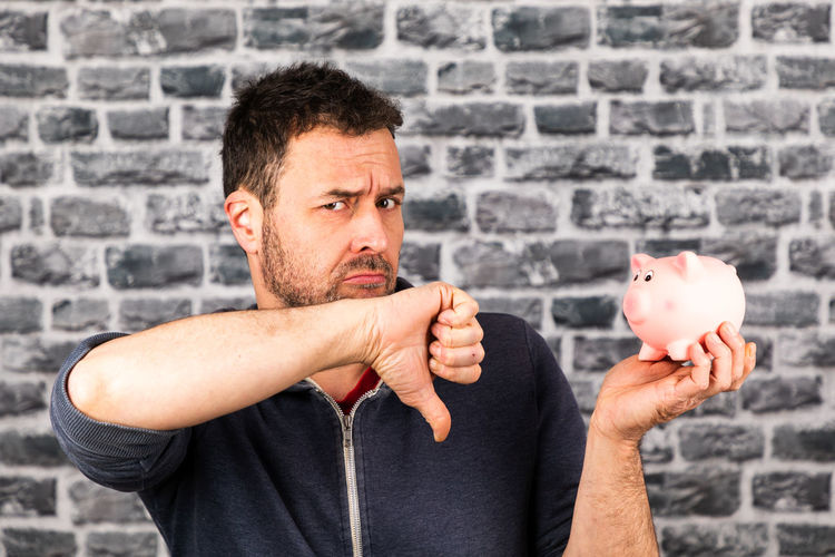 Portrait of man holding piggy back and gesturing against brick wall