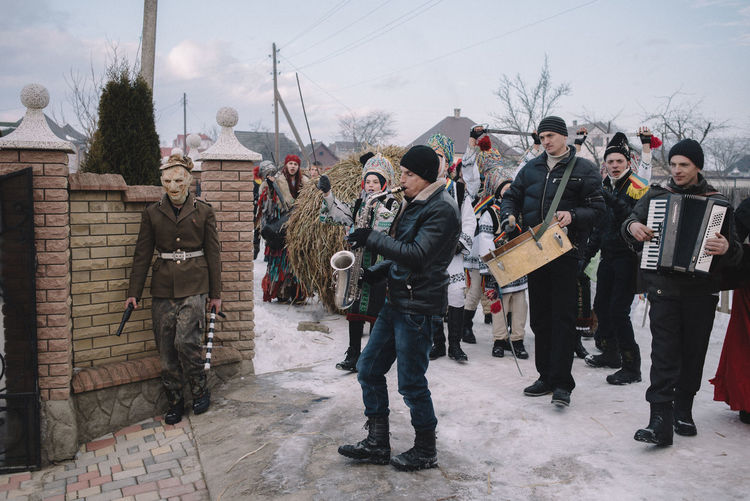 Carnival group walks to the courtyard during the Old New Year celebration. Crasna village, Ukraine. The Photojournalist - 2017 EyeEm Awards