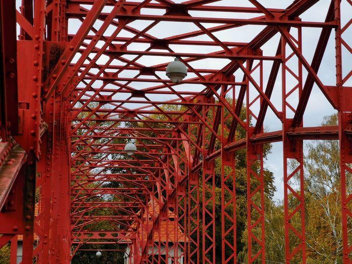 Low angle view of rusty metal bridge against sky