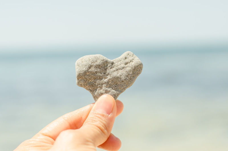 Cropped hand holding heart shape stone against sea