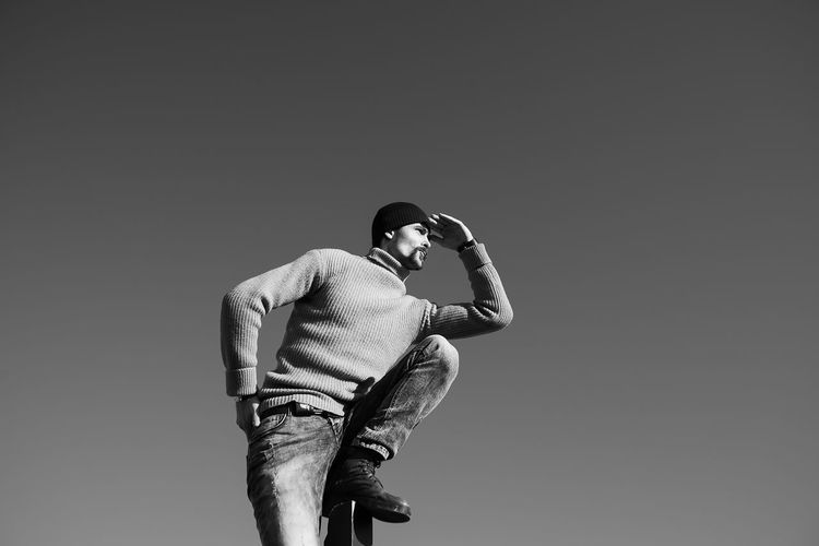 A young man does something interesting. It interacts with a wooden pile on the seashore. One person in the frame. Man on the background of a clear sky. He is warmly dressed in boots, jeans, a sweater and a hat. Casual wear. The guy wears a mustache and stubble. Hair out of the caps. Winter sunny day. Live black and white photo. Lifestyles Lifestyle Authentic Moments Authentic Candid Real People Blackandwhite Black And White Motion Standing Three Quarter Length Men One Person Holding Casual Clothing Leisure Activity Young Men Activity Photography Themes Adult Rear View Young Adult Low Angle View Photographer Obscured Face