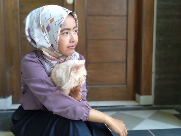 Woman in hijab with cat sitting at home