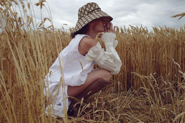Full length of woman crouching at farm