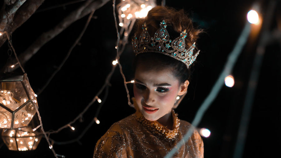 Close-up of beautiful model wearing crown amidst illuminated string lights at night