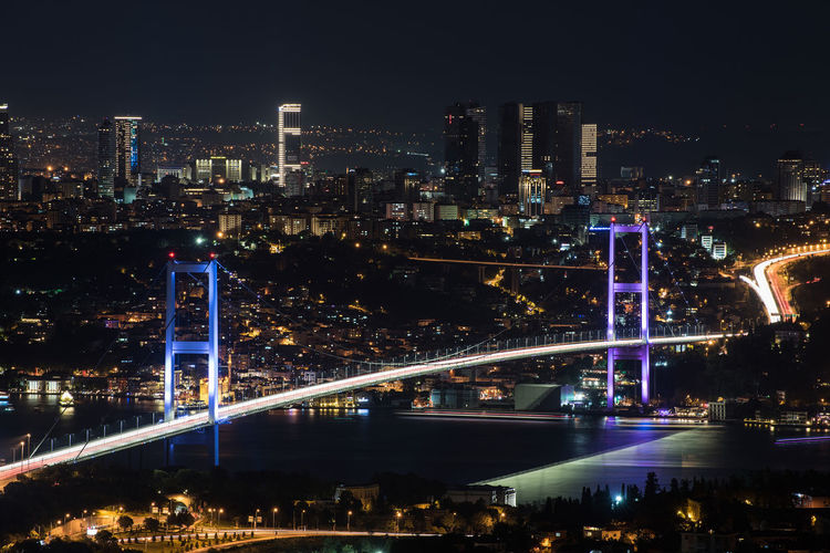 Illuminated bosporus bridge and cityscape at night