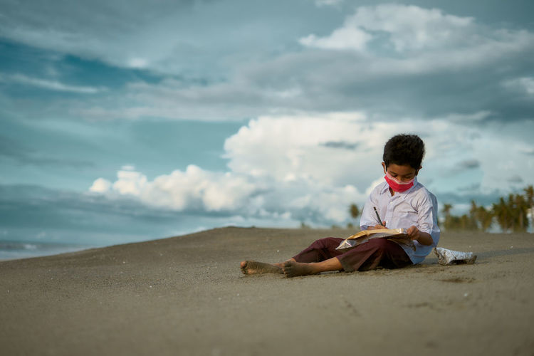 Rear view of boy sitting on shore at beach against sky