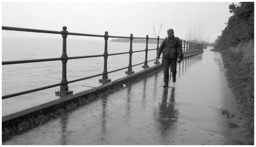 Rear view of people walking on railing