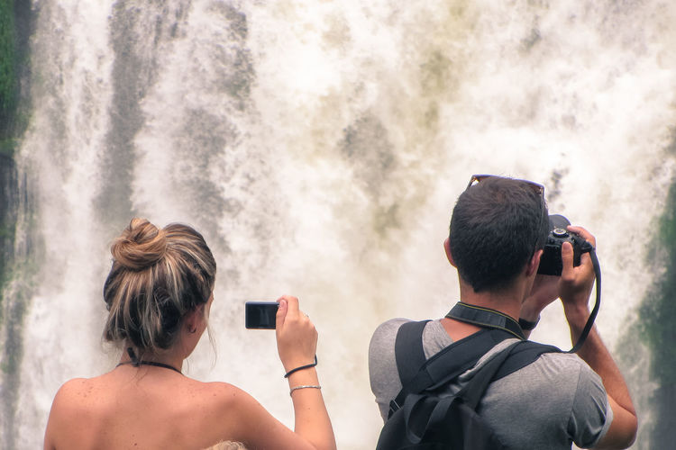 Rear view of friends photographing waterfall
