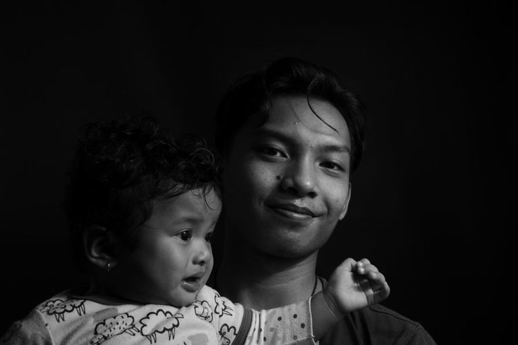 Portrait of brother and sister against black background