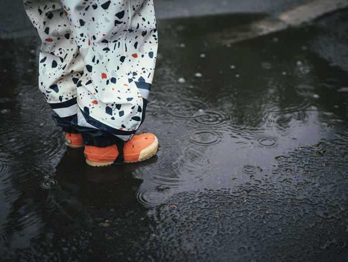 Low section of person standing in puddle