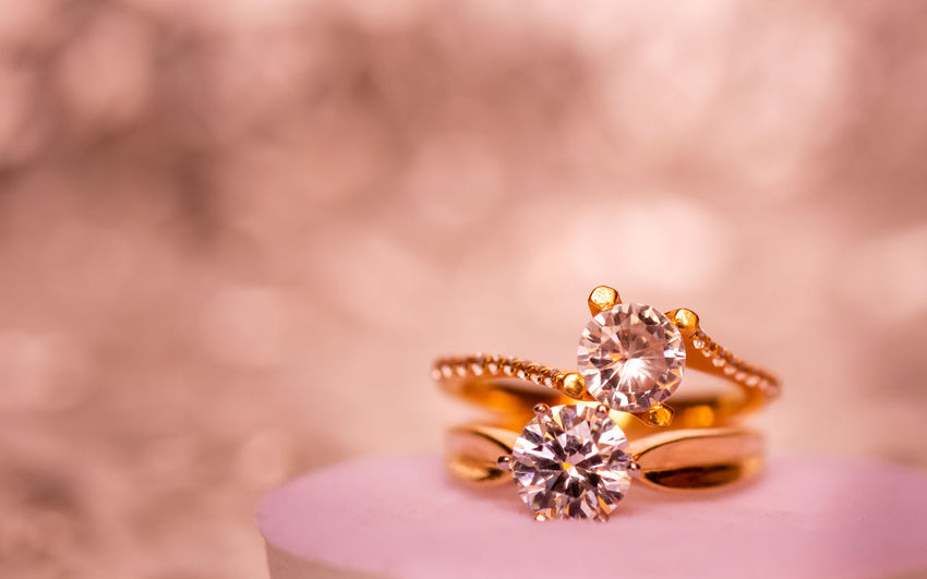 Close-up of wedding rings on red flower