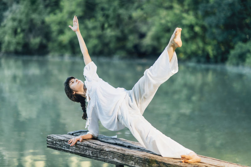 Yoga by the lake. young woman doing yoga exercise plank star pose