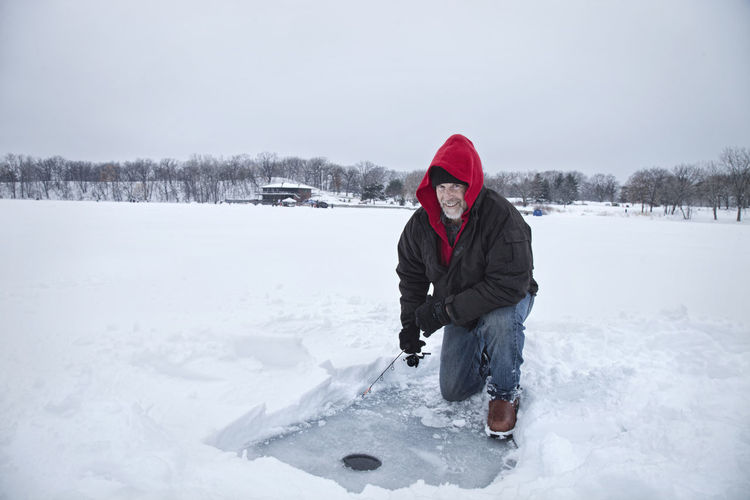 Middle aged man ice fishing on a snowy Minnesota lake One Person Leisure Activity Outdoors Real People Man Middle Aged Fishing Ice Lake Snow Minnesota USA Winter Fishing Rod Hole Cloudy Hood Warm Clothing Shore Caucasian Photography Cold Temperature Copy Space Kneeling Smiling