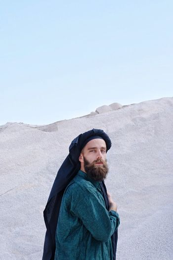 Portrait of bearded young man standing at desert