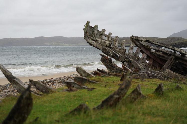 Damaged wood on beach against sky