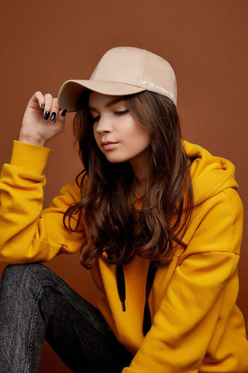Beautiful young woman sitting in hat