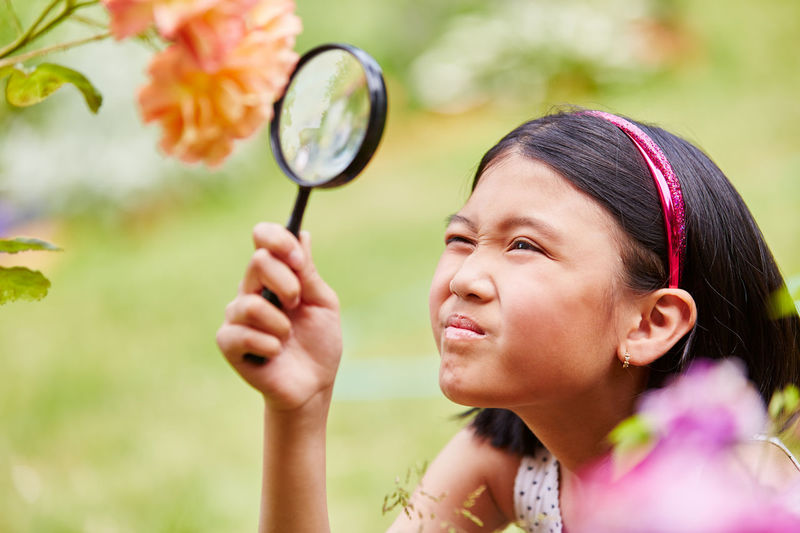 Girl looking at flower through magnifying glass