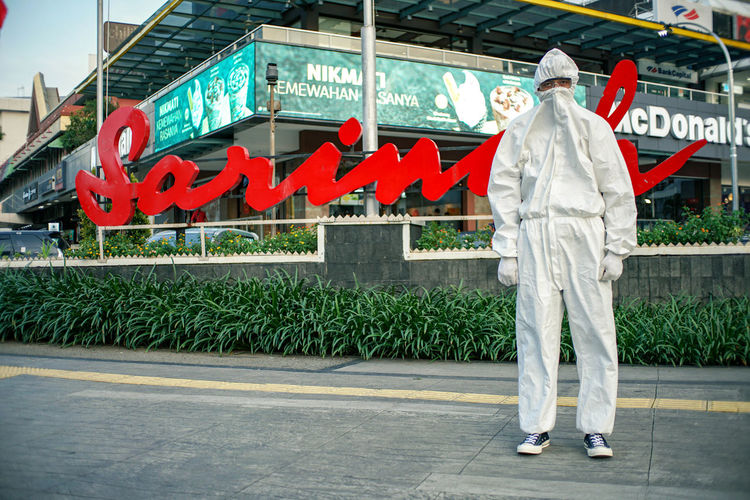 Full length of man standing by bus sign on city