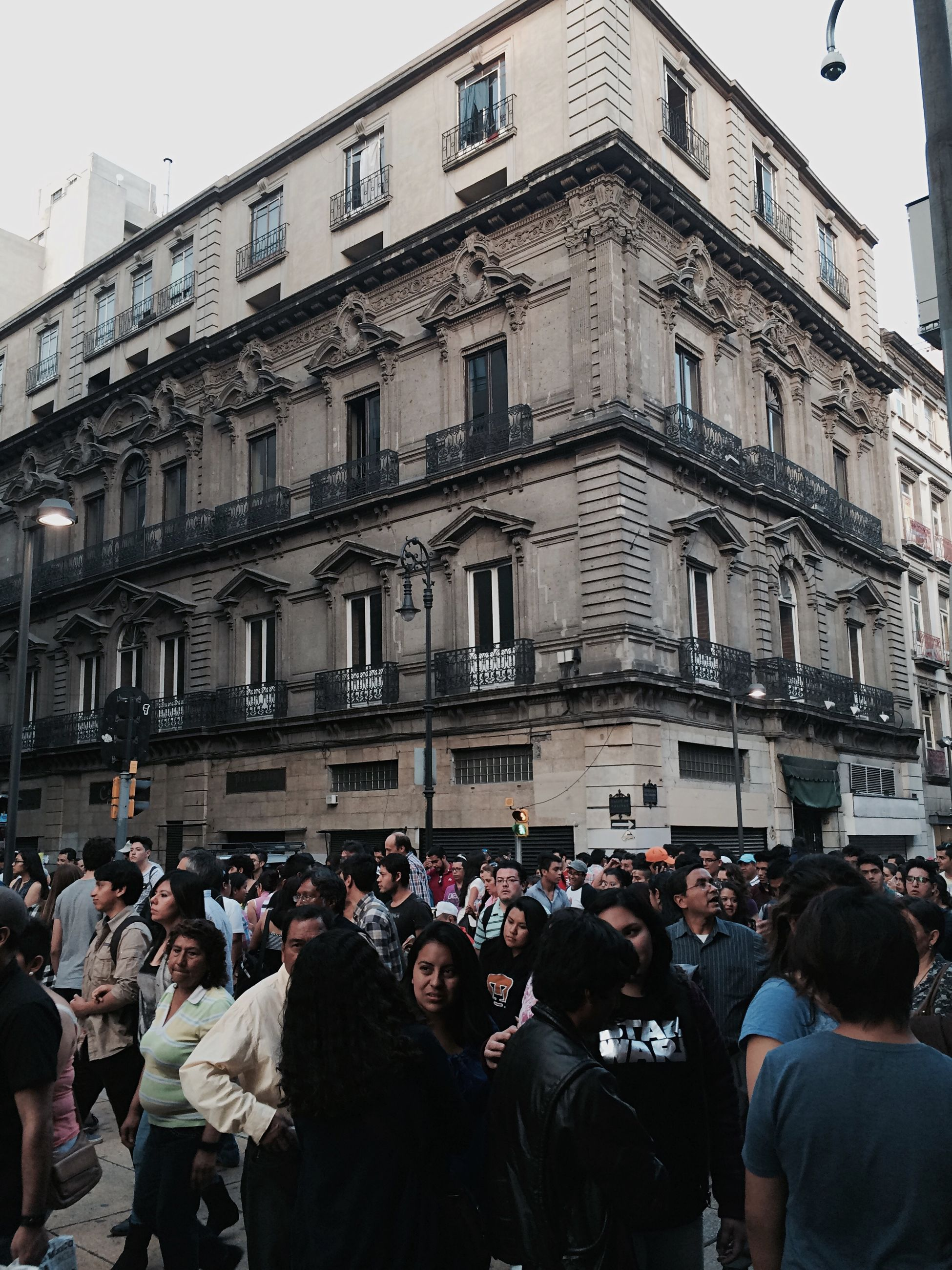 large group of people, building exterior, men, architecture, built structure, lifestyles, person, crowd, leisure activity, street, city life, city, walking, outdoors, day, building, mixed age range, sky, crowded