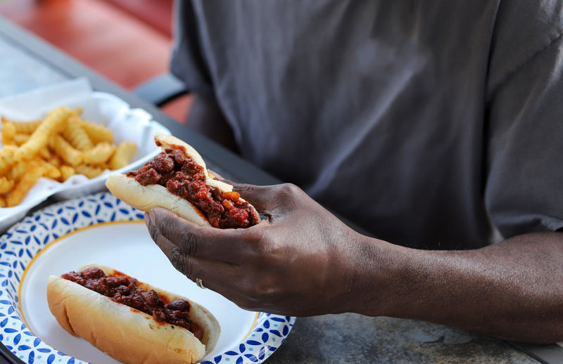 An african-american man eating a chili dog at a picnic