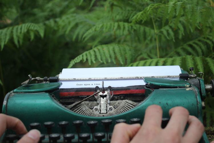 Close-up of hand writing on a typewriter