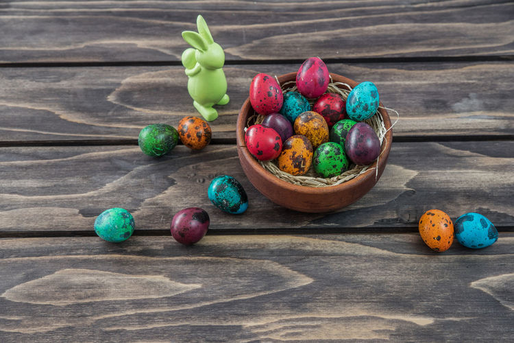High angle view of easter eggs in bowl with bunny on table