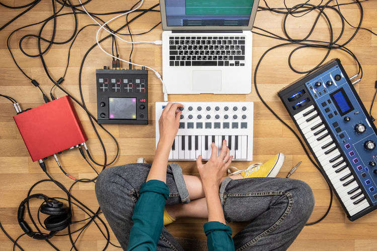 Electronic Music Shots Woman Adult Computer Flooring Headphones High Angle View Human Body Part Indie Indoors  Keyboard Listening Music Musician One Person Producer Rehearsal Sitting Sound Recording Equipment Table Technology Using Laptop Young Adult