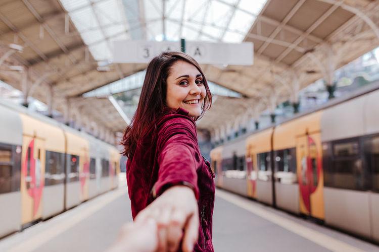 Portrait of beautiful woman standing at railroad station