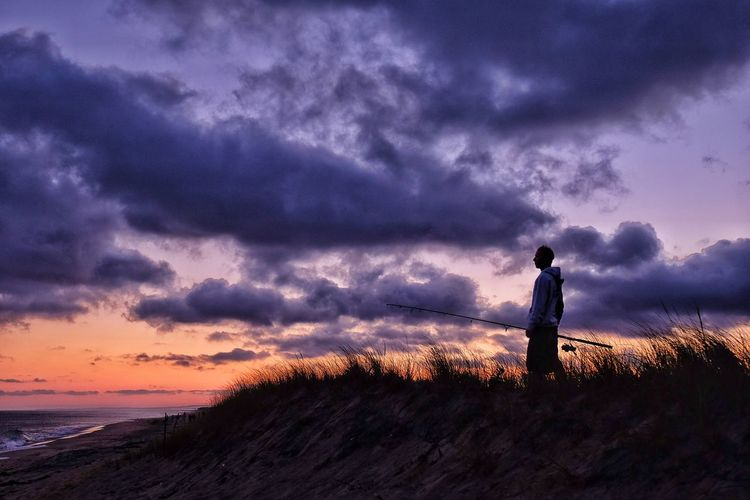Man standing with fishing rod on beach against sky