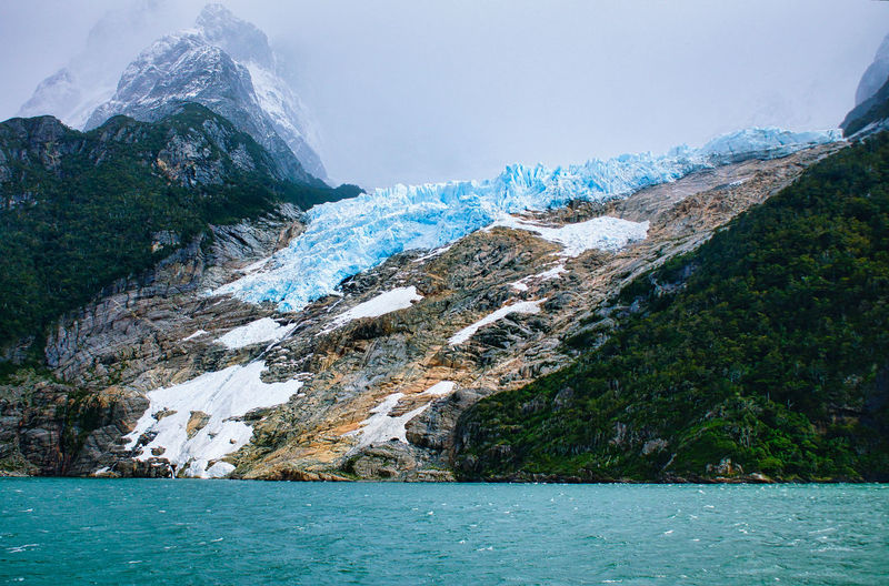 Melting glacier against foggy mountain