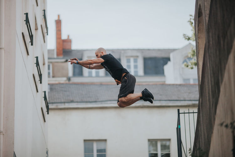 Jumping Shot Parkour Parkour And Free Running Sportsman Arms Raised Building Building Exterior City Day Focus On Foreground Full Length Jumping Leisure Activity Men Mid-air Motion Outdoors Skill  Sport A New Beginning This Is Strength