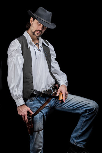 Handsome young man. This is an American cowboy. A vow to a white shirt, brown waistcoat and blue jeans. Black shoes on the feet. Carries a shtyapa, on a belt two pistols. The hair is of medium length; on the face is a beard and mustache. Authentic photo. Culture of America. Cowboy Wild West America American Gun National Authentic Moments Lifestyles Lifestyle One Person Candid Authentic Three Quarter Length Hat Black Background Front View Young Men Young Adult Men Casual Clothing Weapon Handgun Males  Standing Jeans