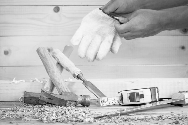 Cropped hands of carpenter wearing glove in workshop
