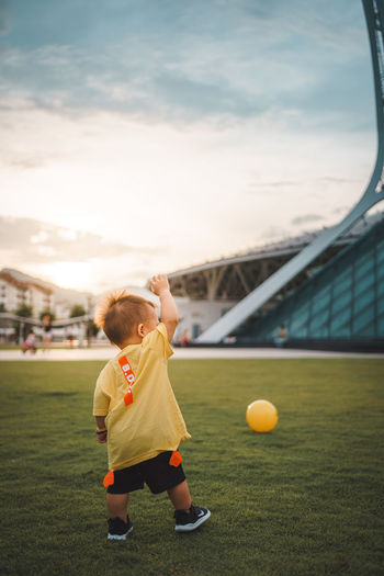 Boy playing with ball in background at sunset