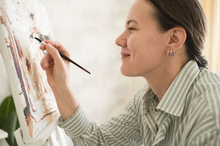 Side view of woman painting at home