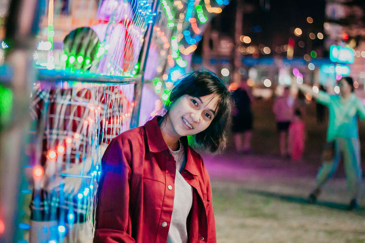 Portrait of smiling young woman against illuminated multi colored lighting equipment