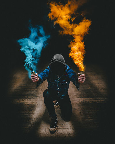 Man holding two smoke bombs indoors. Burning Color Colour Danger Fire Flame Men Night One Person Outdoors People RISK Smoke Smoke - Physical Structure Smoke Bomb