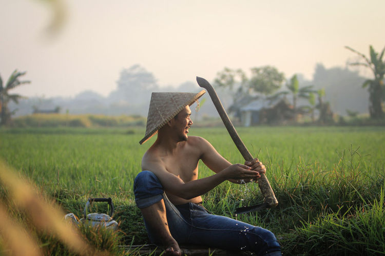 Full length of man sitting in field